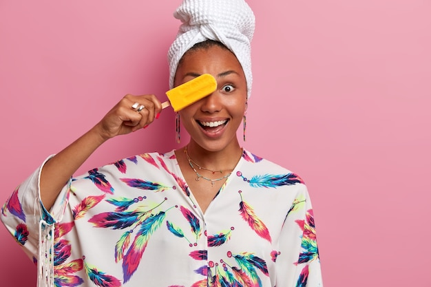 Domestic style and eating desserts. smiling dark skinned young woman covers eye with refreshng yellow ice cream, has fun during summer time, wears dressing gown, poses against pink wall