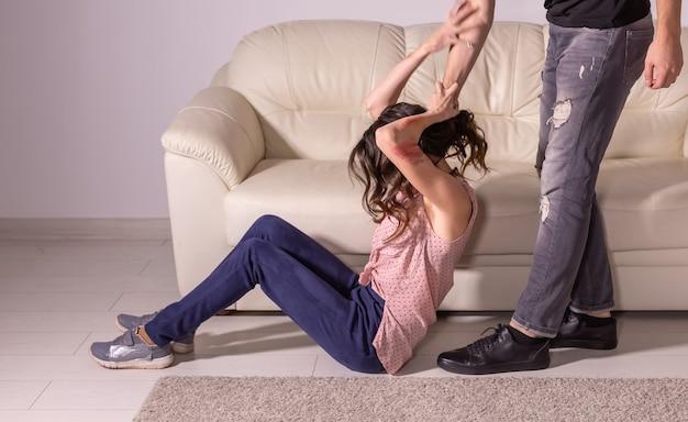 家庭内暴力、虐待、被害者の概念-戦いをしている男性と女性、髪の毛で無力な女性を引きずっている男性