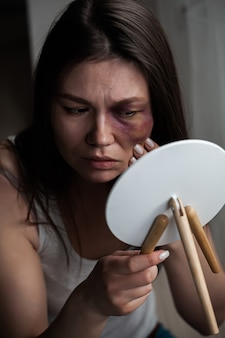 Domestic violence, abuse woman with bruise on face by the window looks in the mirror