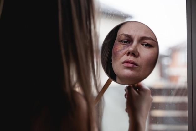 가정 폭력, 창가에 멍이 있는 학대 여성은 거울을 본다