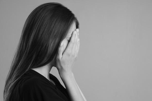 여성에 대한 가정 폭력. 소녀는 손으로 얼굴을 가리고 도움을 요청합니다. 가정 폭력을 중지하십시오.