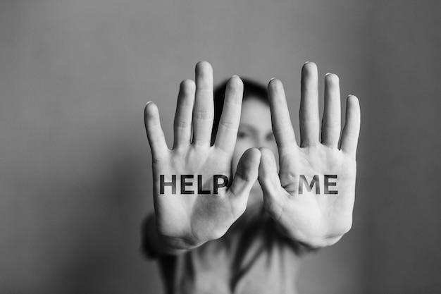 여성에 대한 가정 폭력 소녀는 손으로 얼굴을 가리고 도움을 요청합니다