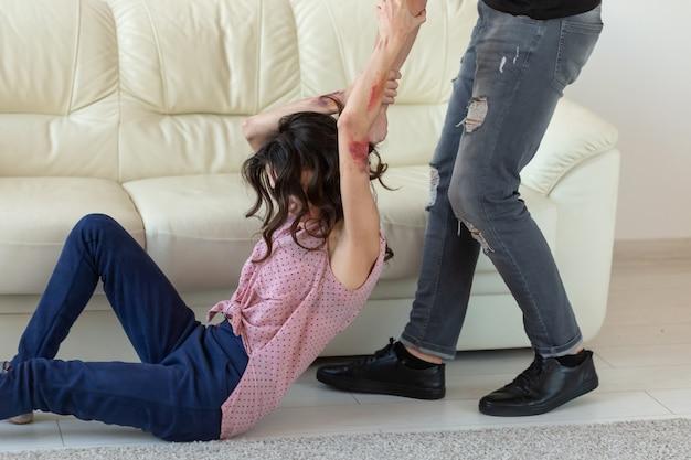 Концепция домашнего насилия, алкоголизма и злоупотребления - агрессивный мужчина хватает свою жену, лежащую на полу.