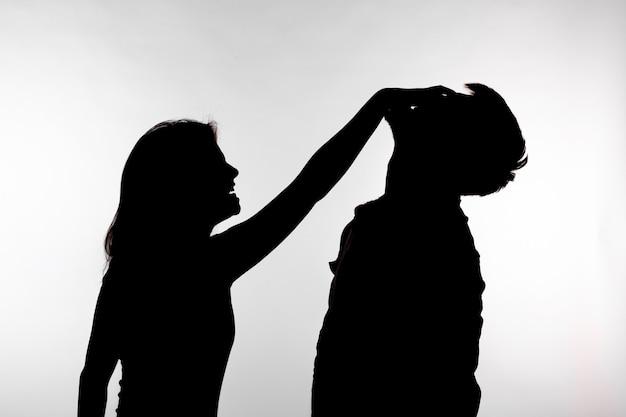 가정 폭력과 학대 개념 - 한 남자를 때리는 여성의 실루엣.