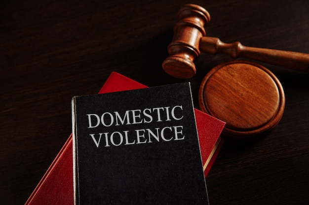 Domestic violence concept. wooden gavel on the big red book