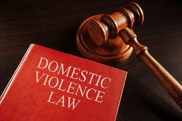家庭内暴力の概念。大きな赤い本の木製のガベル