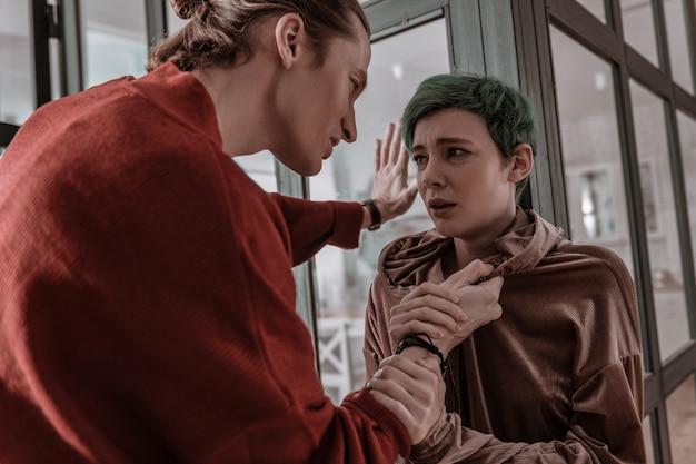 가정 폭력. 가정 폭력으로 고통받는 젊은 부드러운 녹색 머리 여자 친구