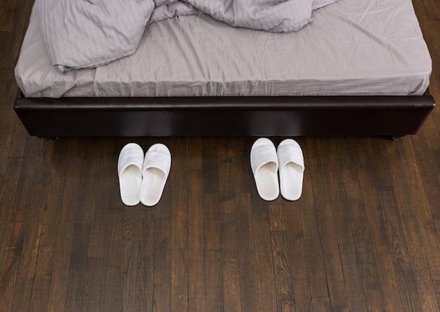 ロフトスタイルの寝室のベッドの横に国産の白いスリッパがあります