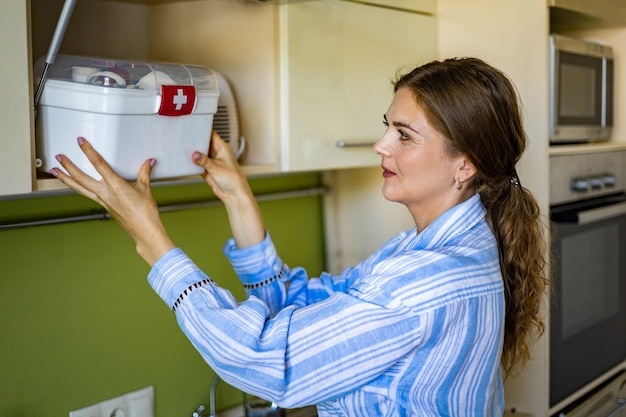 Domestic woman putting first aid kit with vitamins drugs antibiotics and cure at kitchen cupboard