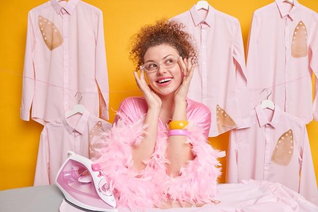 가사 노동 및 가사 개념. 곱슬 머리를 가진 기뻐하는 꿈꾸는 여성은 투명 고글을 착용하고 드레싱 가운은 몽환적 인 표정으로 외모는 옷을 다림질합니다. 행복한 주부