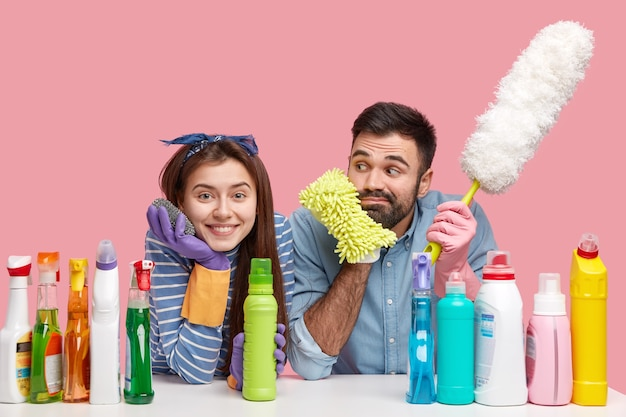 Domestic work concept. happy female and male janitors have positive facial expressions, happy to finish house work, hold sponges and dust brush