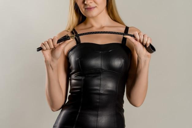 손에 엉덩이와 가죽 드레스에 지배적 인 여자.