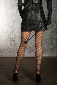 The dominant woman in a leather dress with a spank in her hand back. bdsm outfit