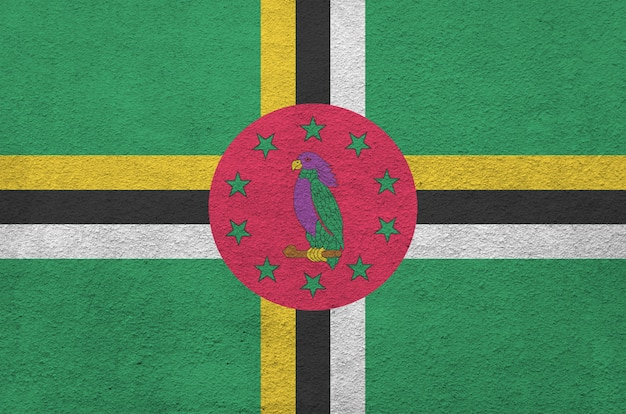 Dominica flag depicted in bright paint colors on old relief plastering wall. textured banner on rough background