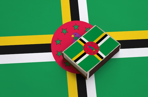 Dominica flag  is pictured on a matchbox that lies on a large flag