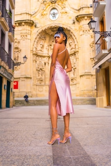 Доминиканская этническая девушка с косами в красивом розовом платье. мода, наслаждающаяся летом в красивой церкви города