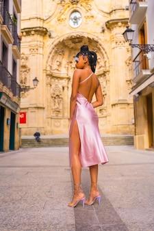 Доминиканская этническая девушка с косами в красивом розовом платье. мода наслаждаясь летом в красивой городской церкви, вертикальное фото