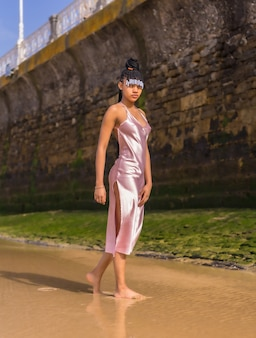 Доминиканская этническая девушка с косами в красивом розовом платье. мода, наслаждаясь летом, гуляя по пляжу