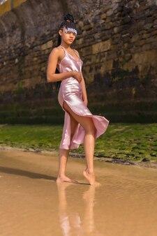 Доминиканская этническая девушка с косами в красивом розовом платье. модное позирование, наслаждаясь летом на пляже