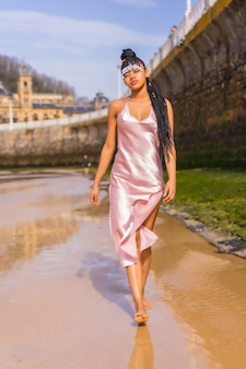 Dominican ethnic girl with braids with a beautiful pink dress. fashion enjoying the summer walking on the beach