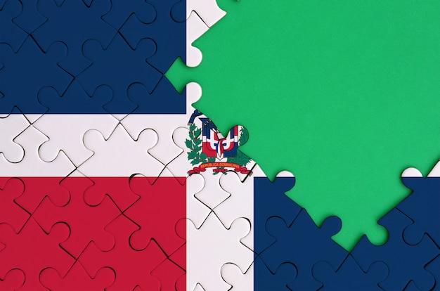 도미니카 공화국 국기는 오른쪽에 무료 녹색 복사 공간이있는 완성 된 직소 퍼즐에 그려져 있습니다.