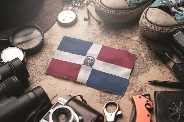 Dominican republic flag between traveler's accessories on old vintage map. tourist destination concept.
