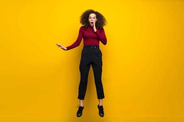 Dominican woman with curly hair jumping over isolated yellow wall