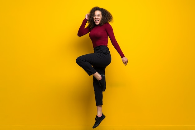 Dominican woman with curly hair jumping  on yellow wall