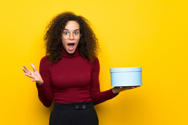 Dominican woman with turtleneck sweater holding gift box in hands