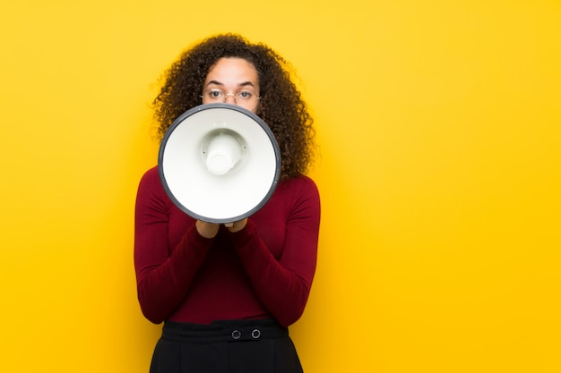 Dominican woman with turtleneck sweater shouting through a megaphone