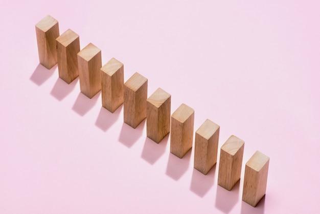 Домино-блок. домино беспрерывно рушится на розовом фоне.
