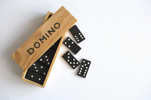 Игра домино в деревянной коробке на белой предпосылке, взгляд сверху. семейная настольная игра
