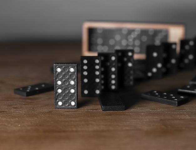나무 상자 케이스가 있는 나무 테이블에 있는 도미노 게임 조각
