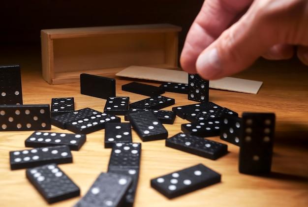 Фишки домино разбросаны по деревянному столу с деревянной коробкой