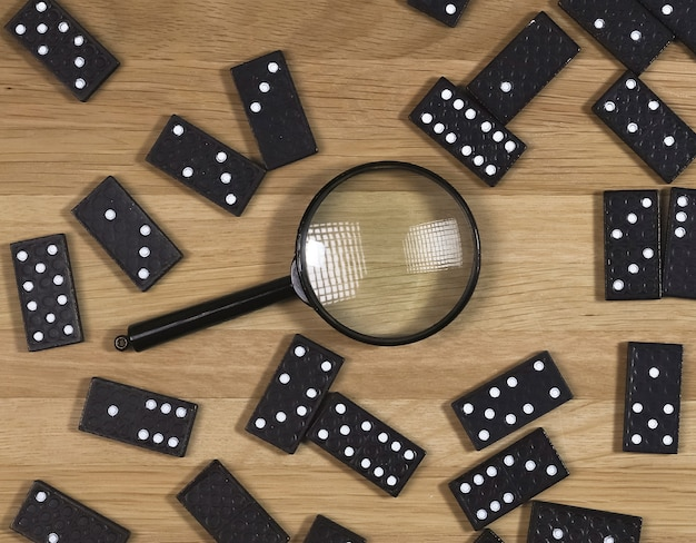 Domino game pieces scattered on wood desk with magnifying glass top view
