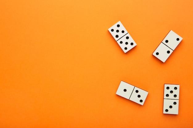 Кусочки домино на оранжевой поверхности с копией пространства