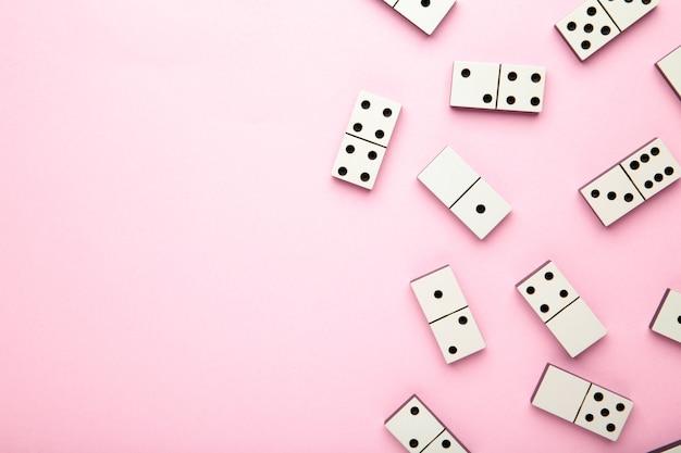 Кусочки домино на розовой поверхности с копией пространства