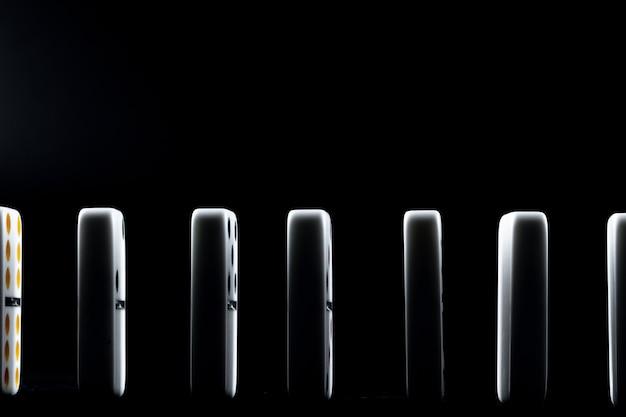 Кусочки домино в ряд на черной поверхности