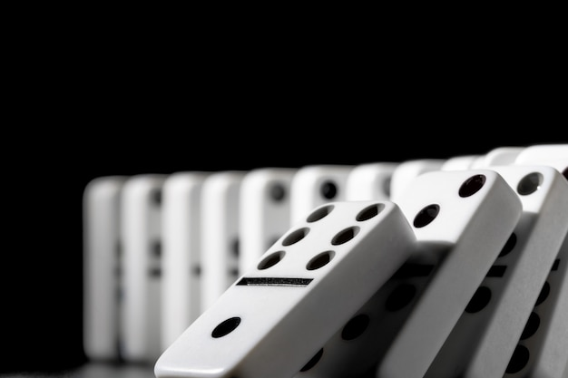 Domino pieces put in a row on black background