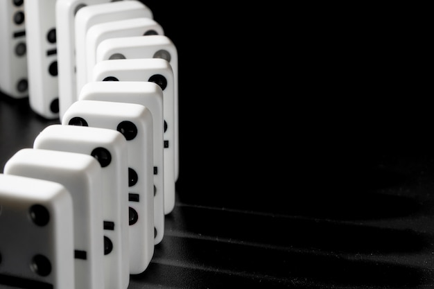Domino pieces put in a row on black surface