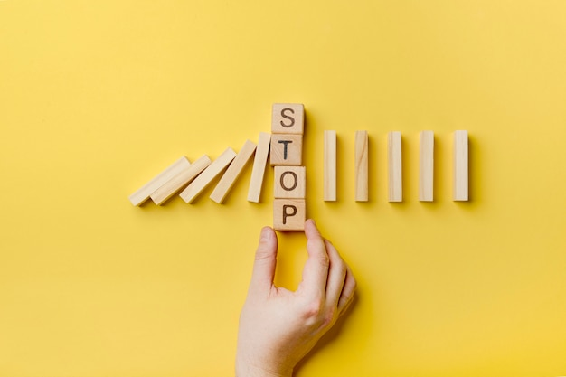 Domino wooden blocks with stop message