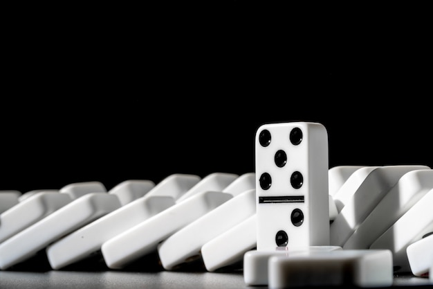 Dominoes standing in a row on black