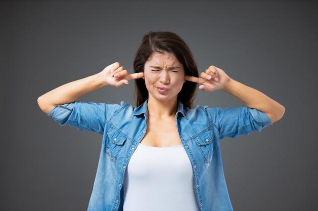 Не беспокойте меня, сейчас не время для разговоров. девушка в повседневной одежде закрывает уши пальцами и щурится, чтобы избежать зрительного контакта. незрелое поведение молодого человека