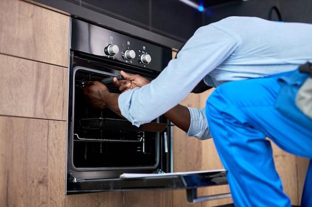 수리를 미루지 마십시오. 도구 도구를 사용하여 부엌에서 오븐을 검사하는 측면 보기 아프리카 수리공. 집에서 일하는 동안 파란색 작업복 작업복을 입은 자신감 있는 전문 흑인 수리공
