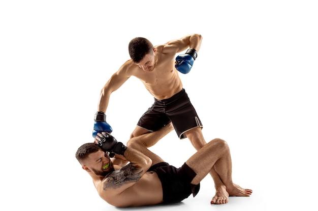 あきらめないでください。白いスタジオの背景に孤立してポーズをとる2人のプロの戦闘機。健康な筋肉質の白人アスリートまたはボクサーのカップルが戦っています。スポーツ、競争、人間の感情の概念。