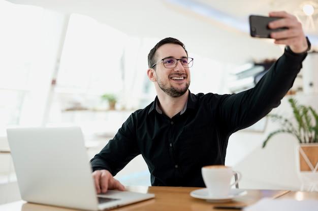 先延ばしにしないでください!彼は集中問題の概念を動作する必要があるときに笑顔の男は自分撮りを取ります。男は彼が今日どこで働いているか彼の友人に示します。ソーシャルメディアコセプト。背景に明るい喫茶店。