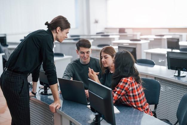 リラックスしないでください。近代的なオフィスで働くカジュアルな服装の若い人たちのグループ