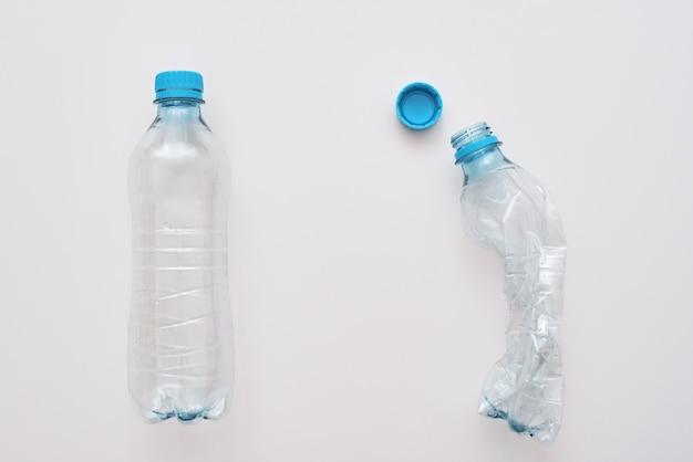 あなたの世界をスクラムしないでください。ペットボトル2本、1本は崩れています。廃棄物管理とリサイクル。ごみの分別の概念