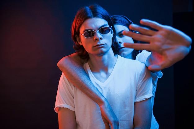 Не трогай моего брата. портрет близнецов. студия снята в темной студии с неоновым светом