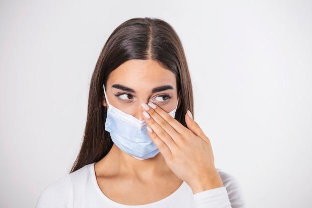 顔に触れないでください。汚れた手で目をこすりながらサージカルマスクを着用している女の子。